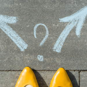 Yellow Women's Shoes on Pavement with 2 Blue Chalk Arrows and a Question Mark
