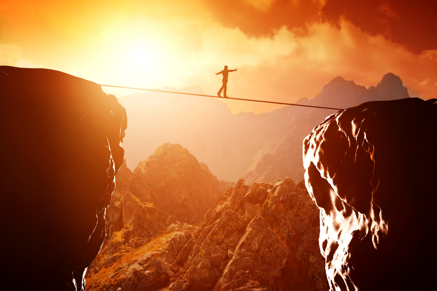 Person Walking Tightrope Over Canyon At Sunset