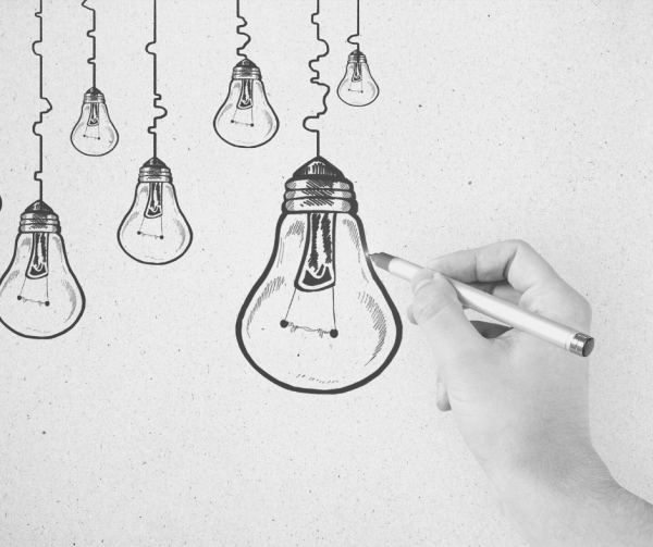 Person drawing lightbulbs with pencil